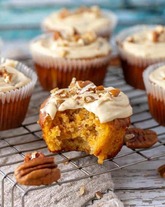 shot of carrot cake cupcakes on a wire rack, one with a bite taken out. pecan nuts scattered around