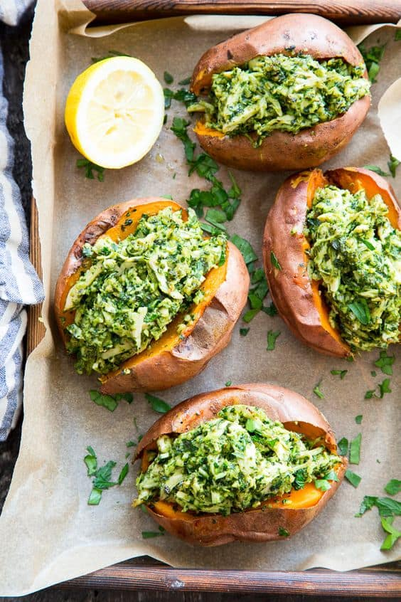Pesto chicken stuffed sweet potatoes on brown parchment paper topped with fresh herbs on a dark gray background, with a fresh halved lemon in the top left corner.