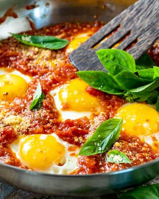 close up of eggs in purgatory in a stainless steel pan with a wooden spatula and fresh basil leafs
