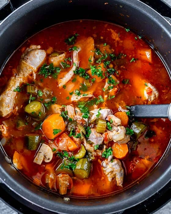 Top shot of instant pot chicken stew topped with fresh herbs in a slow cooker.