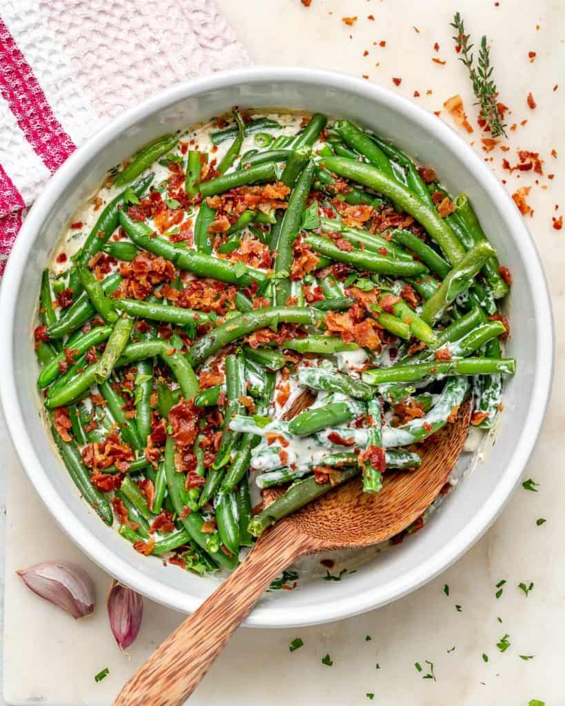 Garlic and herb creamy green beans topped with bacon bits in a white bowl on a beige surface.