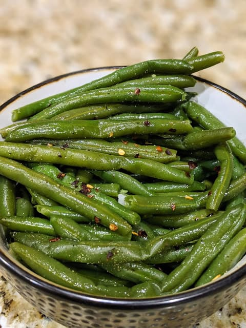 Garlic butter frozen green beans in a black bowl with a brown textured background.