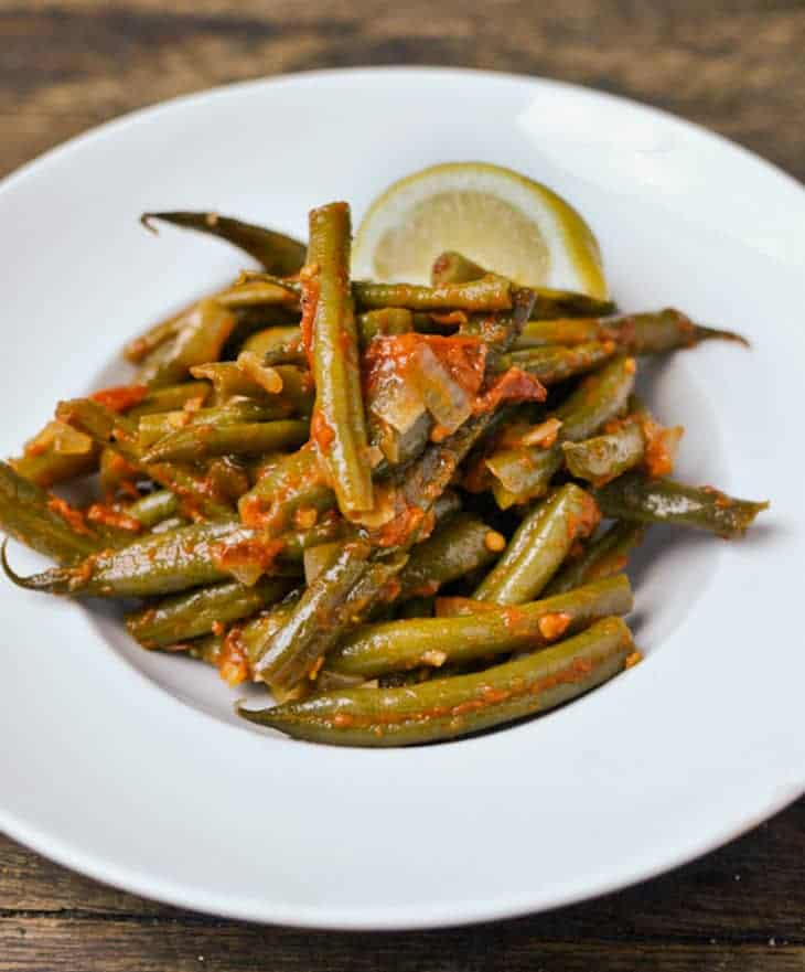 Greek-style braised frozen green beans in a white plate with a brown background.