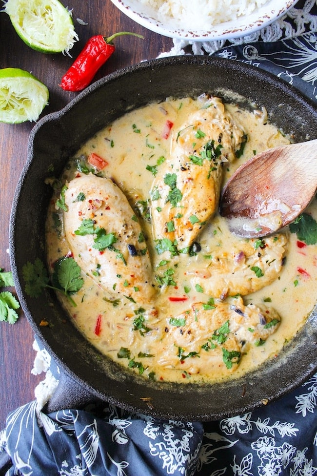 Coconut lime chicken topped with fresh herbs in a black skillet on a wood surface surrounded by fresh ingredients.