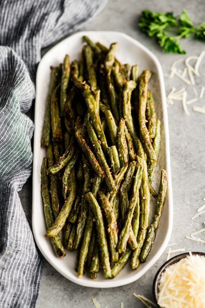 Parmesan roasted green beans in a long white plate with fresh grated cheese to the side on a gray surface.
