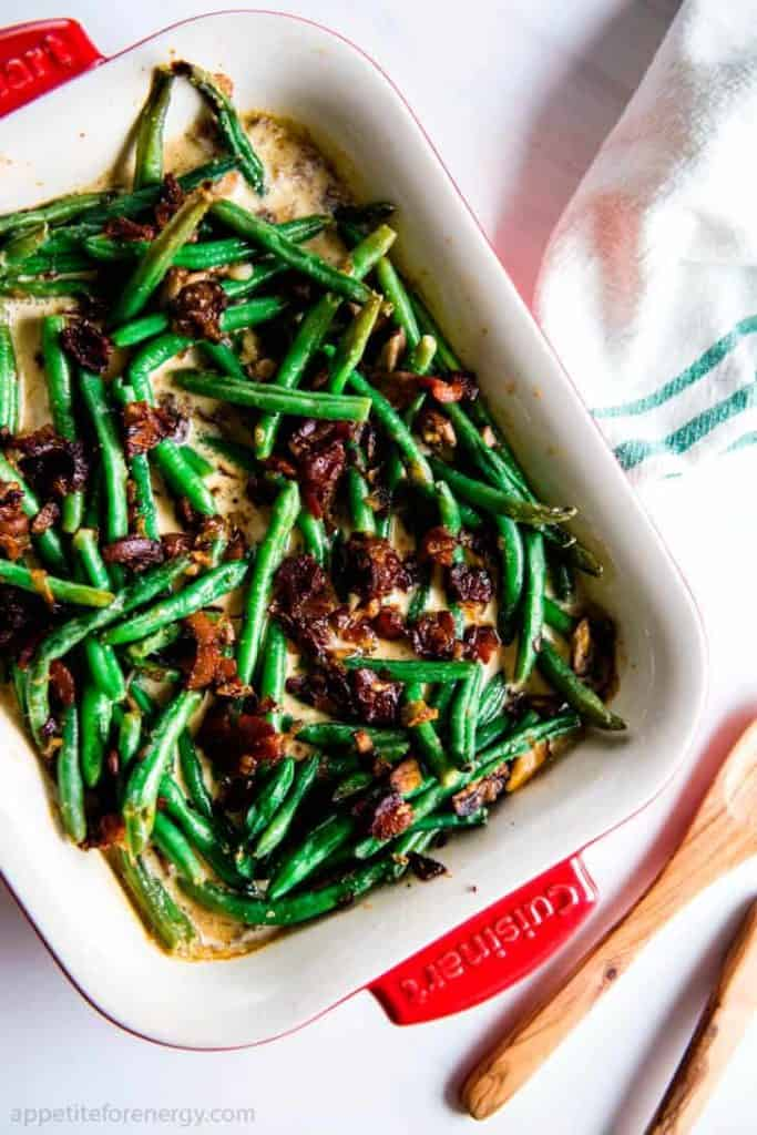Sautéed frozen green beans with bacon cream sauce in a square baking dish on a white kitchen towel.