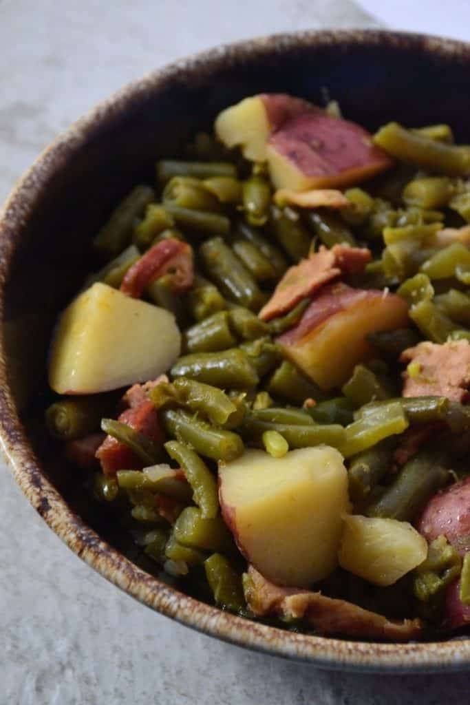 Southern style frozen green beans in a brown bowl with a beige background.