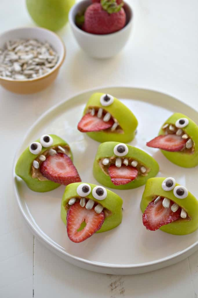 Healthy Halloween apple bites arranged on a white plate on a white table.