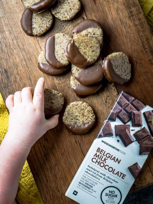 Healthy no bake cookies on a wooden platter with a bar of chocolate to the side.