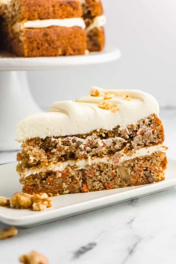 Carrot cake keto Thanksgiving dessert in a white plate on a marbled tabletop with a white background.