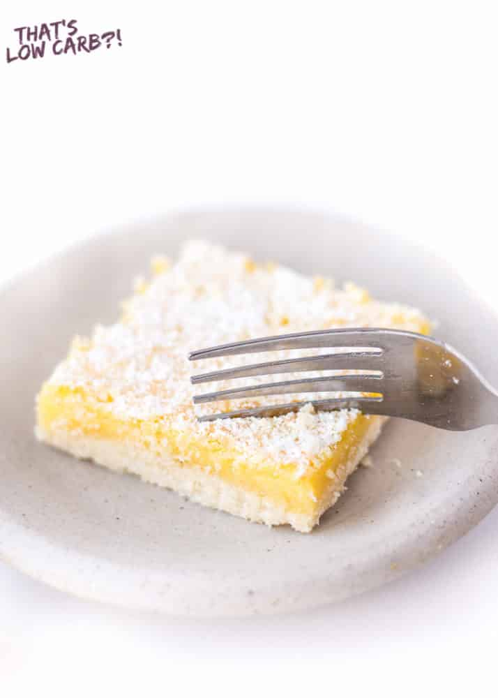 Keto lemon bar topped with powdered sweetener in a gray plate on a white surface.