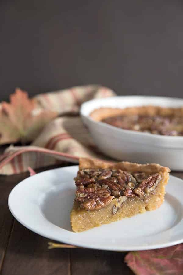 Sugar free pecan pie on a white plate on a wooden surface.