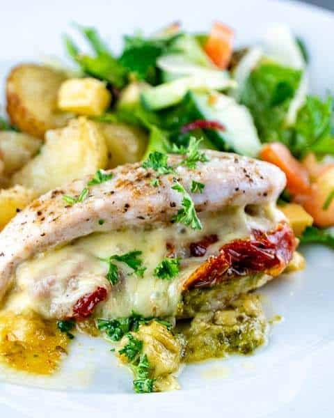 Front shot of caprese stuffed chicken breast topped with fresh herbs.