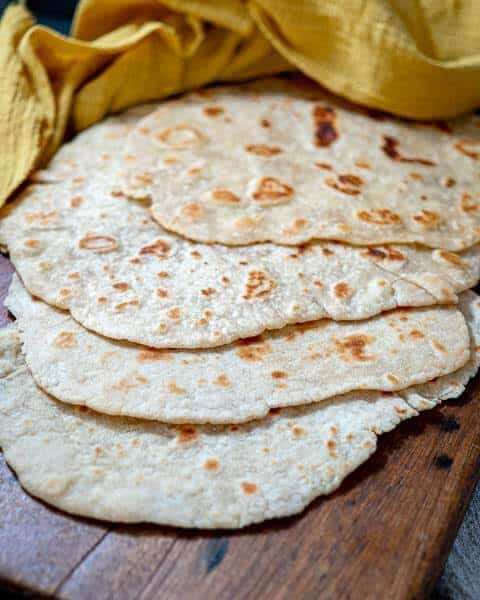 Top shot of stack of sourdough flatbreads on a wooden board with a yellow kitchen towel at the top of the frame.
