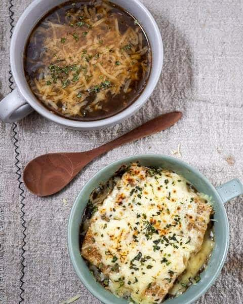 Two bowls of french onion soup on a gray background, one bowl of soup without bread at the top and one bowl with bread and cheese at the bottom. There is a wooden spoon on the surface between them.